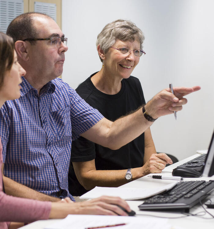 A couple sit beside a librarian, pointing to a computer screen