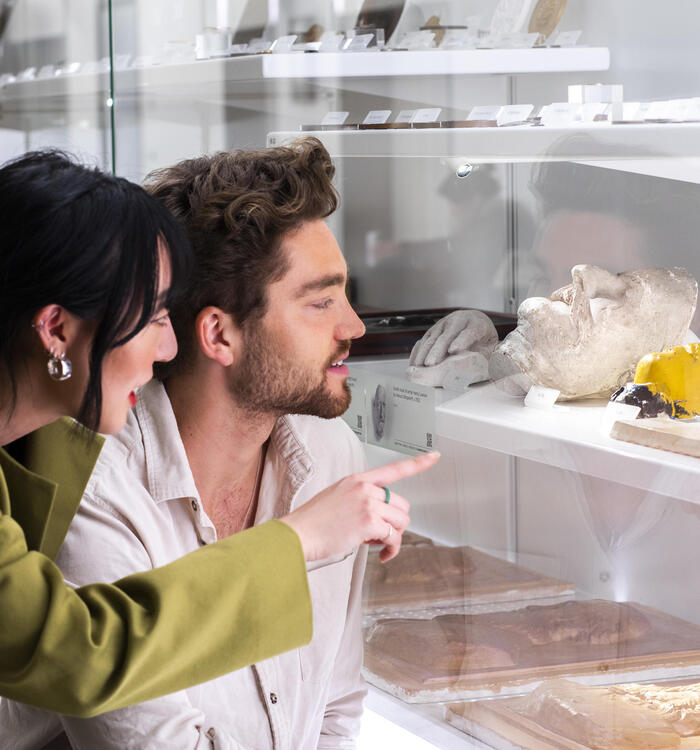 A woman and a man browsing miscellaneous objects in a display shelf.