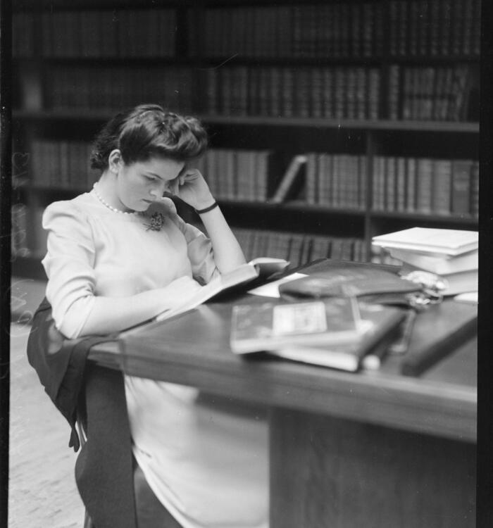 Black and white image of lady reading as a desk