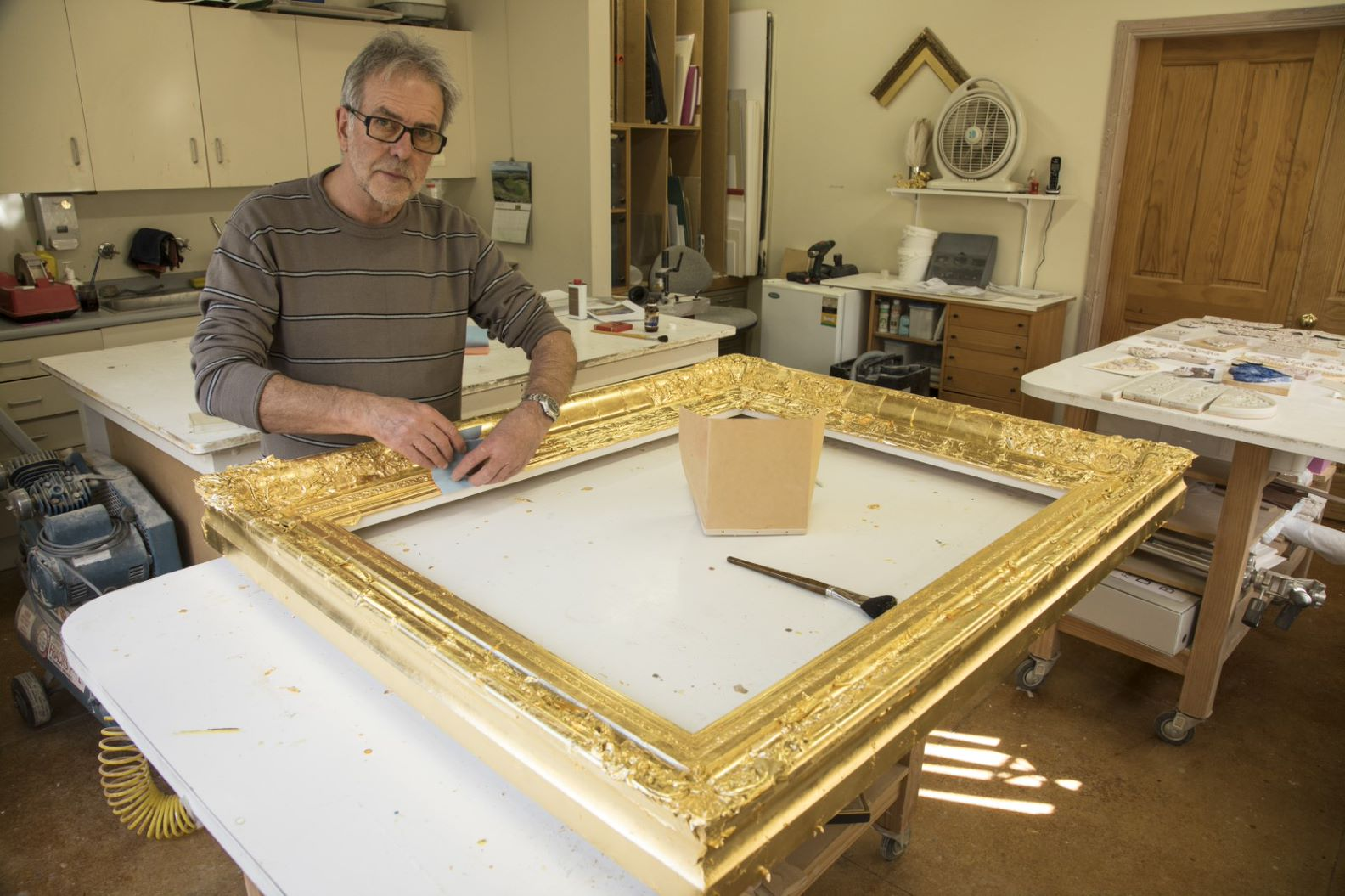 David Butler prepares a new frame for the painting