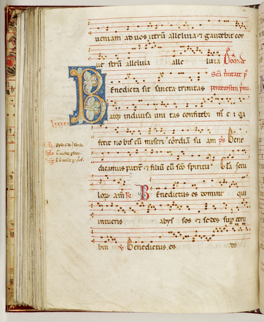 A page of a medieval looking manuscript with lines of music accompanied by Latin lyrics.