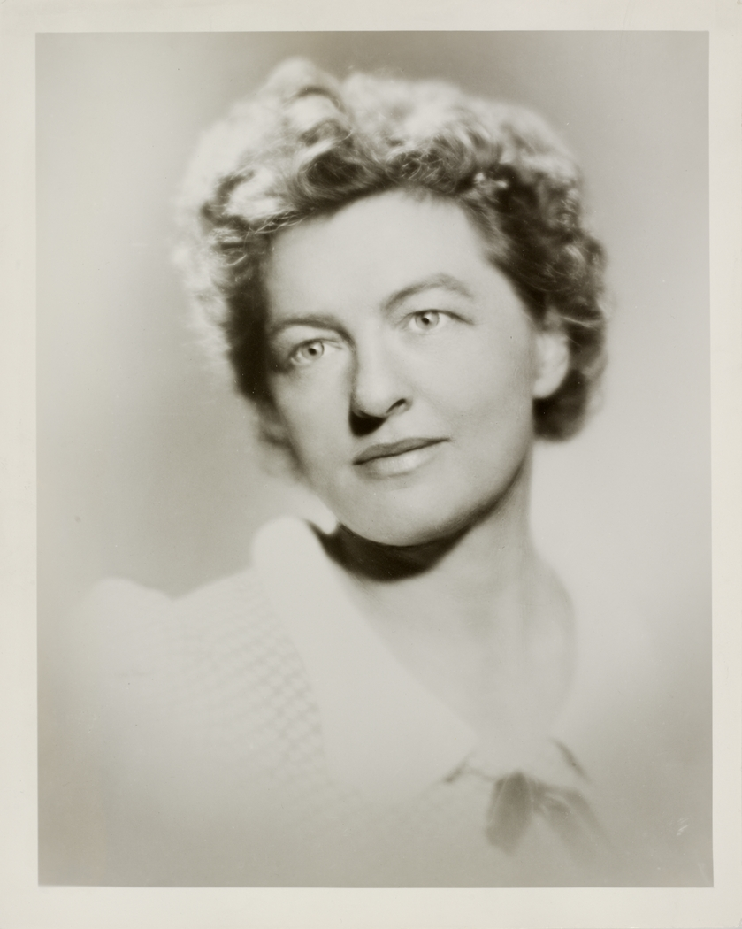 Aged looking black and white photographic portrait of a woman wearing a white blouse with rounded collar.