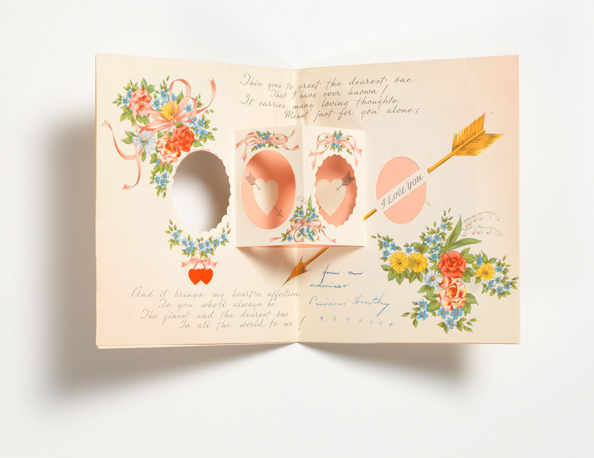 The inside of a Valentine's Day greeting card, with a pop-up feature, a printed romantic message and flower graphics.