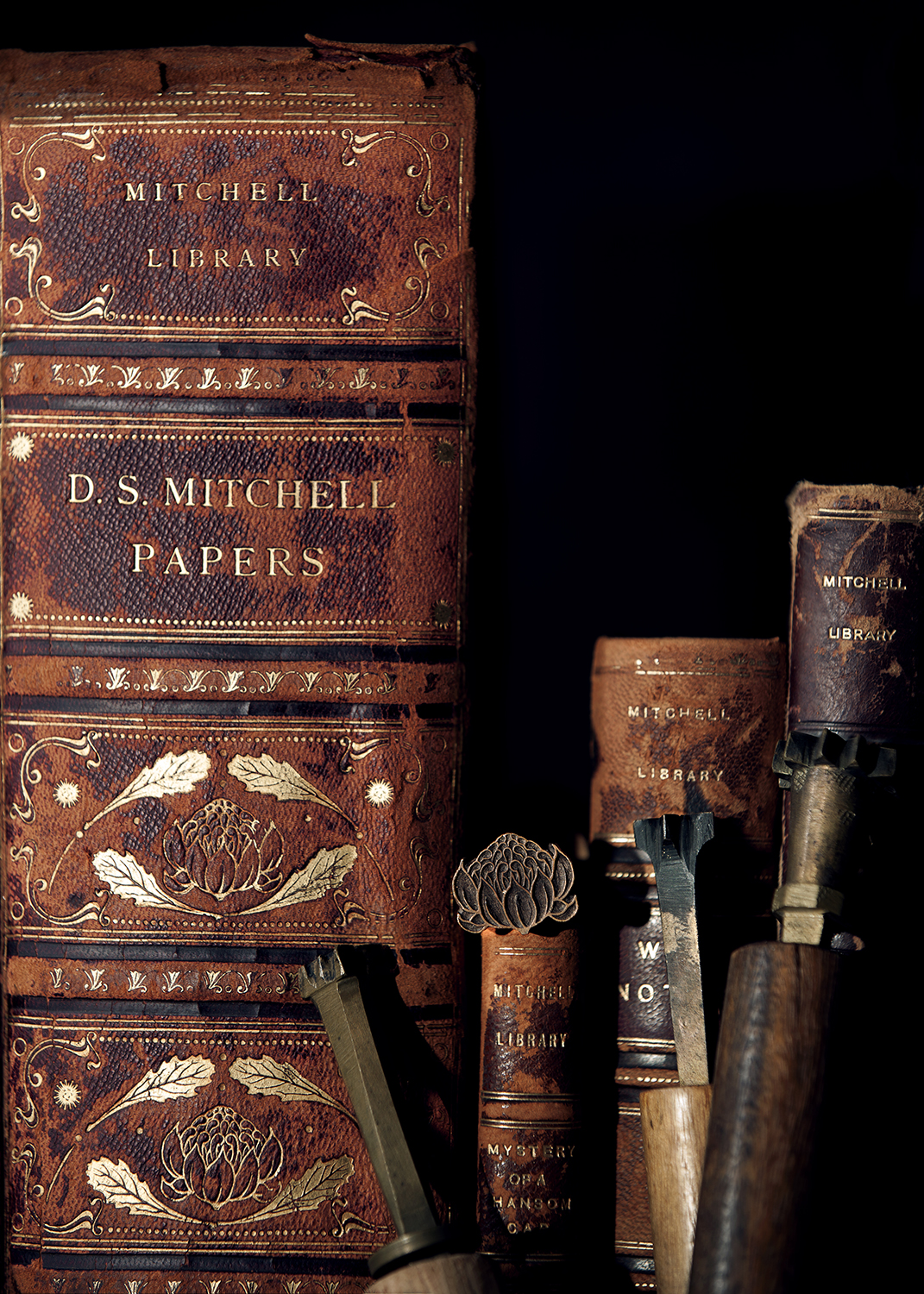 The spines of old books with gold waratah imprints are shown alongside the metal binding tools that created the impressions.